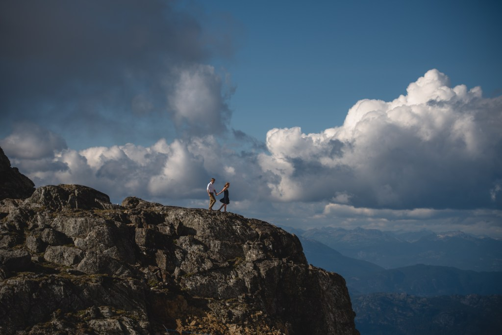 A couple walking on Whistler peak with a blue sky