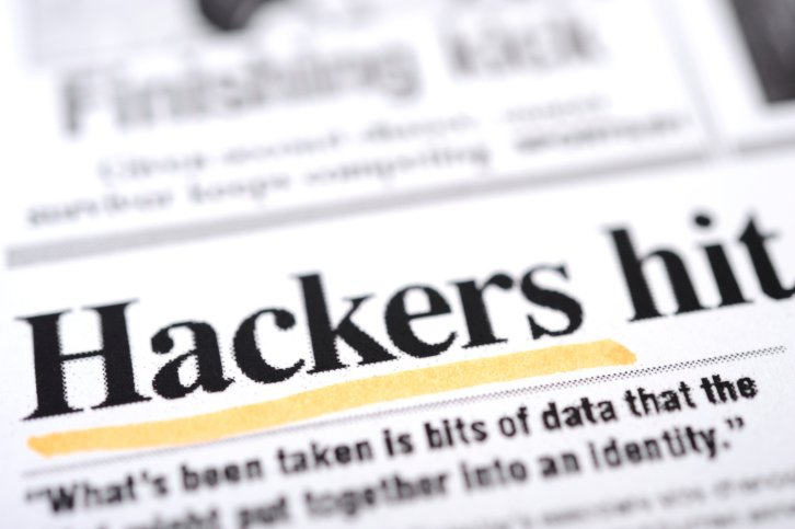 Snippet from a newspaper with the headline Hackers hit with Hackers underlined with yellow highlighter representing importance of IT security solutions