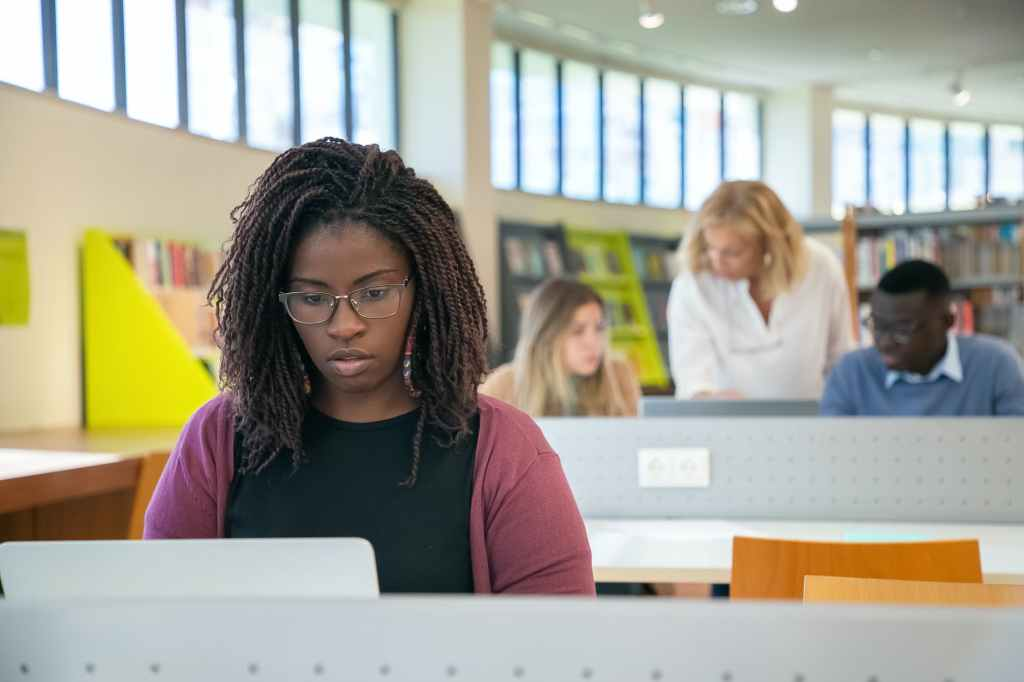 focused multiracial students doing presentation in library with teacher