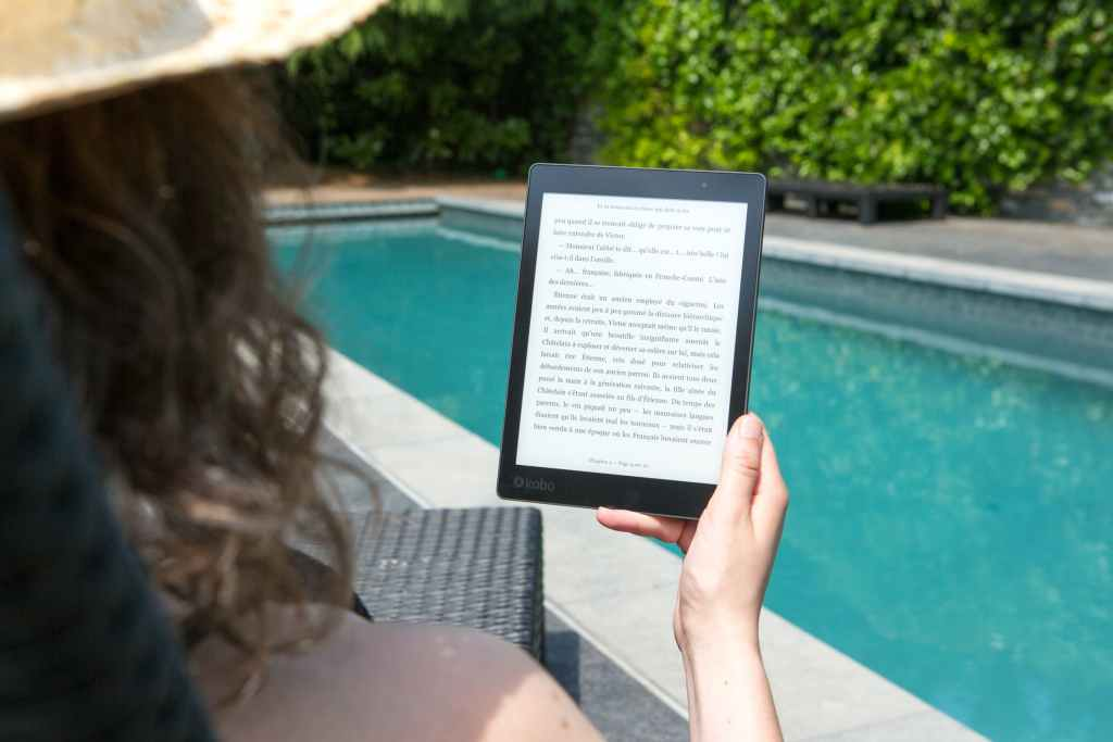 Woman using an eReader with Pool in background
