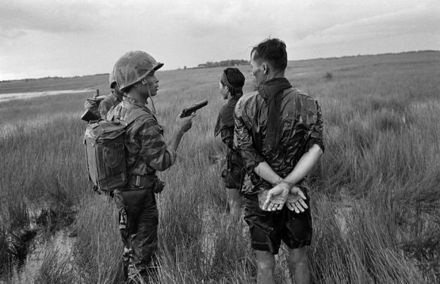 A South Vietnamese soldier holds a cocked pistol as he questions two suspected Viet Cong guerrillas captured in a weed-filled marsh in the southern delta region late in August 1962. The prisoners were searched, bound and questioned before being marched off to join other detainees. (AP Photo/Horst Faas)