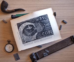 Linogravure noire placée dans un décor d'objets anciens et représentant une tête de macareux moine avec le texte watch the police