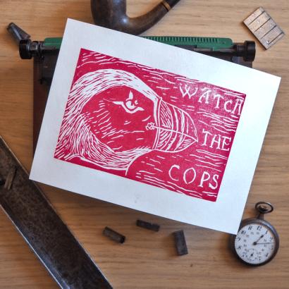 Linogravure rouge placée dans un décor d'objets anciens et représentant une tête de macareux moine avec le texte watch the police