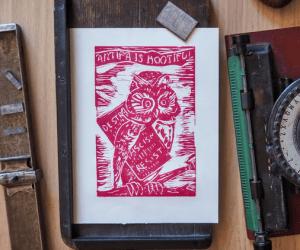 Linogravure rouge placée dans un décor d'objets anciens et représentant une chouette antifa avec une batte de baseball