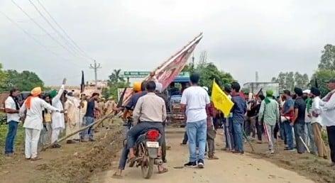 तिकुनिया (खीरी) में घटना स्थल पर लगी होर्डिंग उखाड़ते किसान।