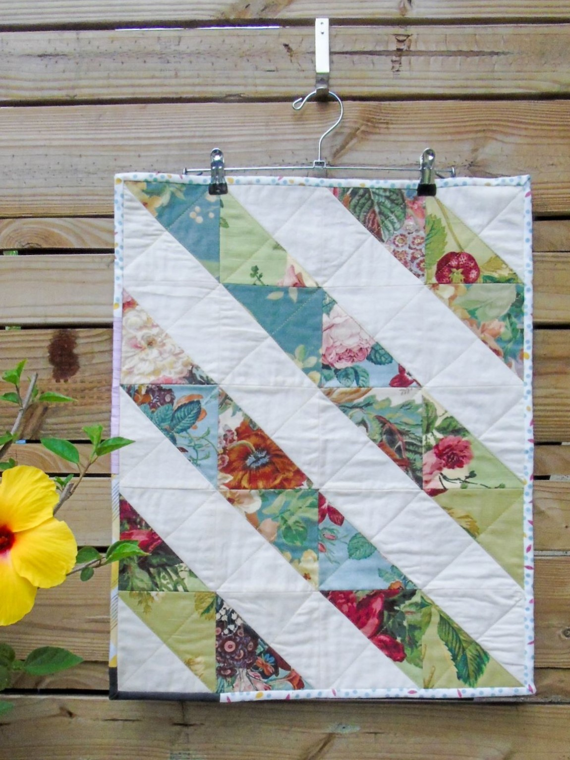 doll or wall hanging quilt with diagonal patchwork stripes using designer fabrics by lola & sofia