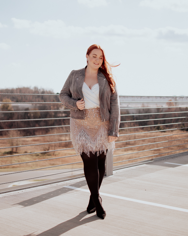 curvy charlotte blogger with red hair wearing suede moto jacket, plus size bodysuit and sequin skirt.