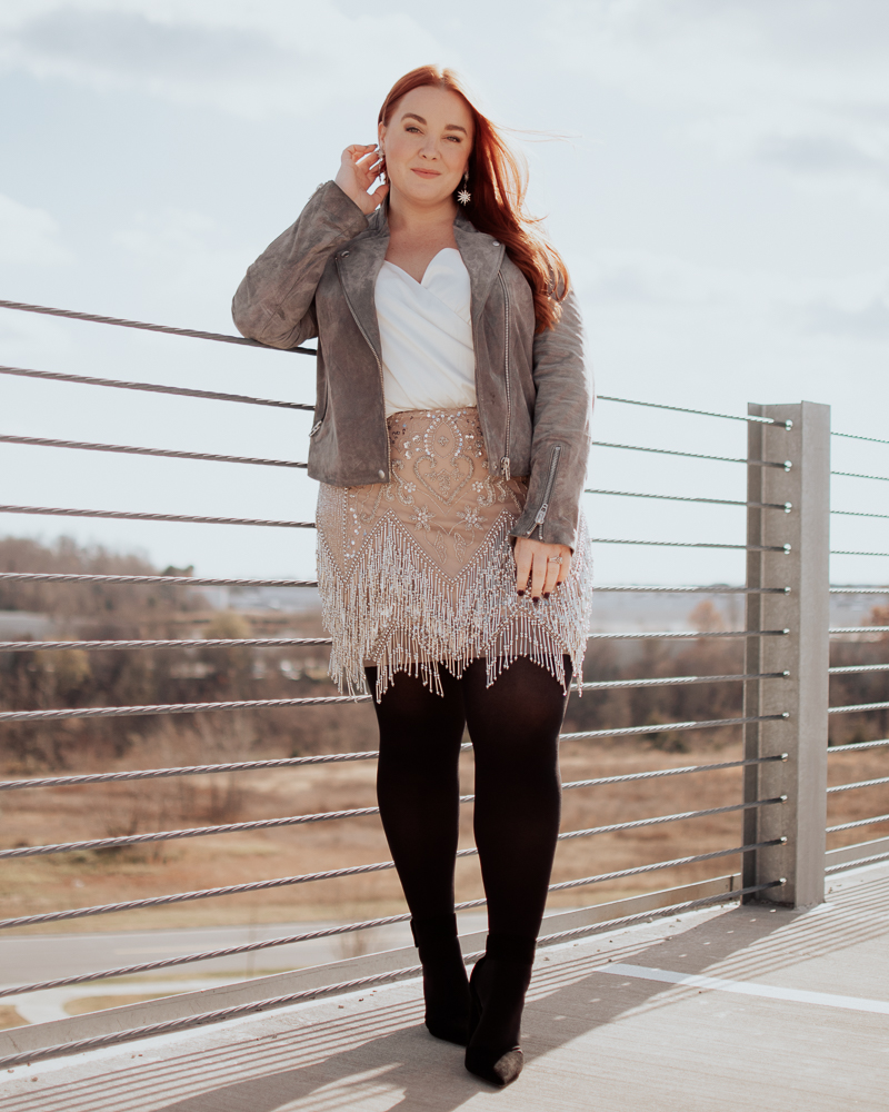 curvy blogger wearing suede moto jacket, plus size bodysuit and sequin skirt.