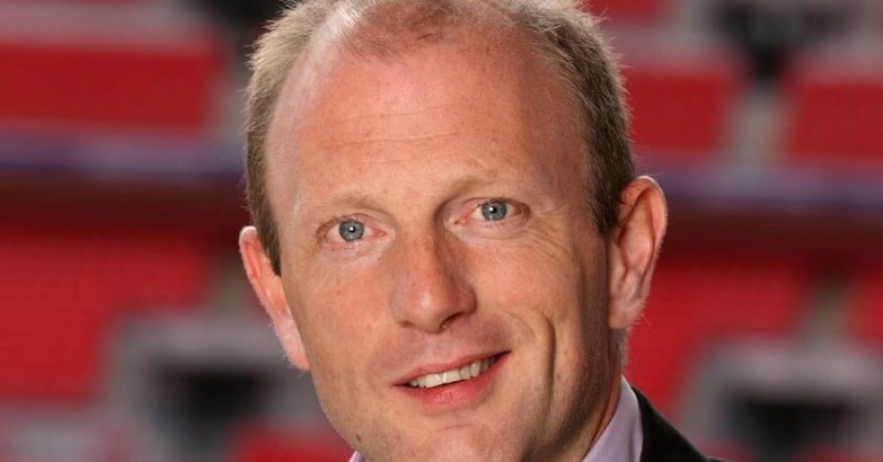 Image of celebrity football commentator, Peter Drury wearing a smile