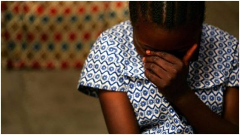 Black young girl with head bowed in distress
