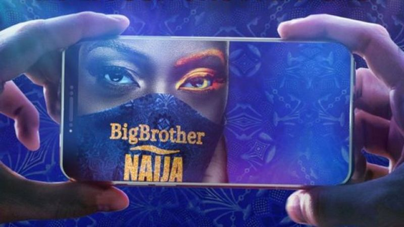 Hand holding a phone with a lady wearing a BBNaija mask.