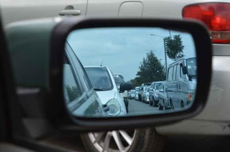 Car side mirror showing a trail of traffic