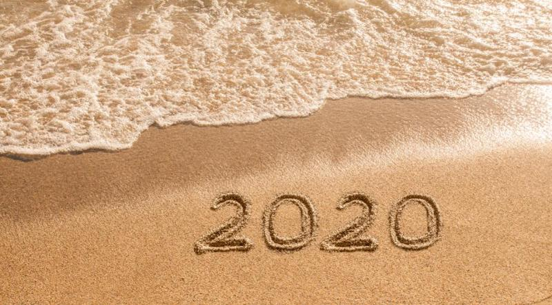 The numbers 2020 engraved on the beach sand with waves sweeping ashore