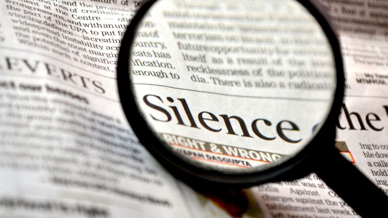 "Looking at the word ""Silence"" in the newspaper through a magnifying glass"