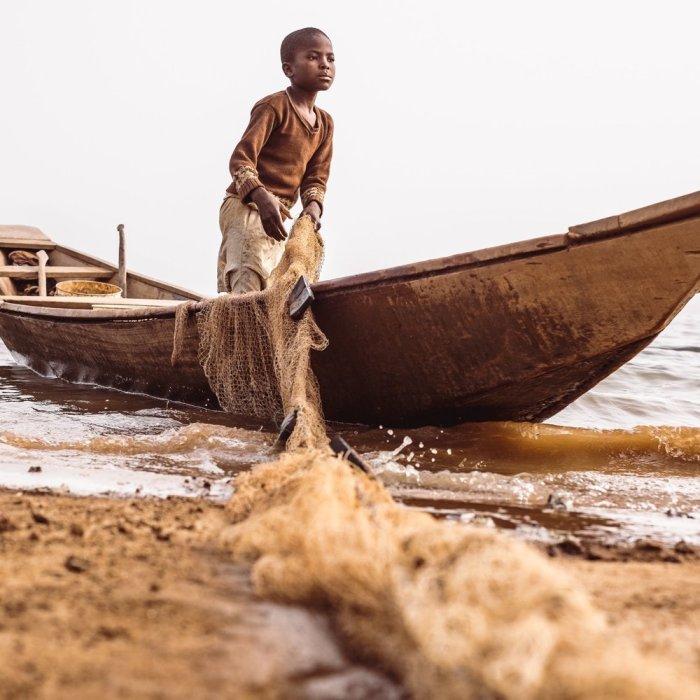 Little boy ashore letting down his net on a canoe