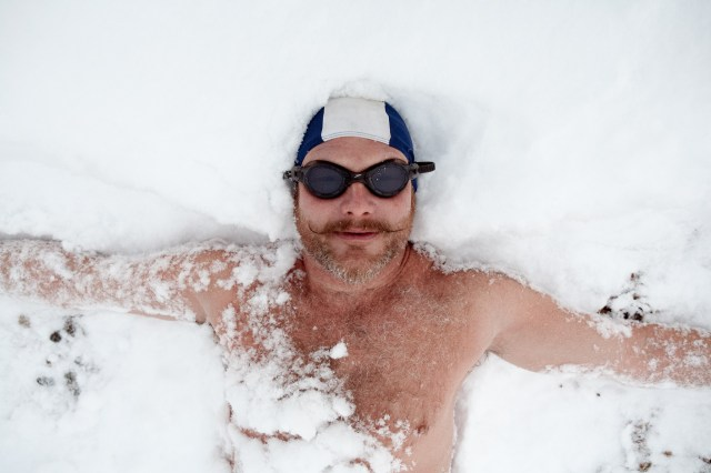 Swimmer lying in snow after a swim in the sea on Brighton beach