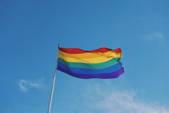 A rainbow flag against a blue sky with clouds