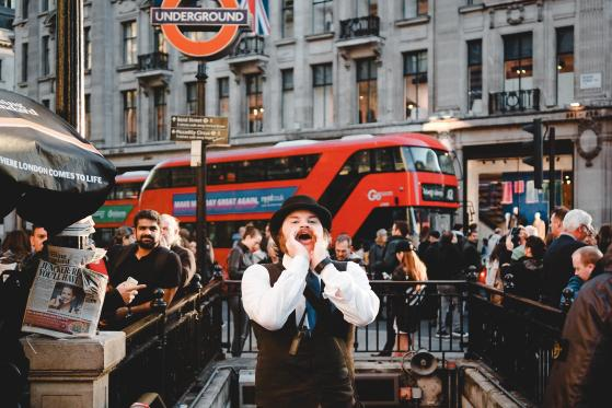 Man cupping his hands around his mouth and shouting at crowds by a London Underground Station
