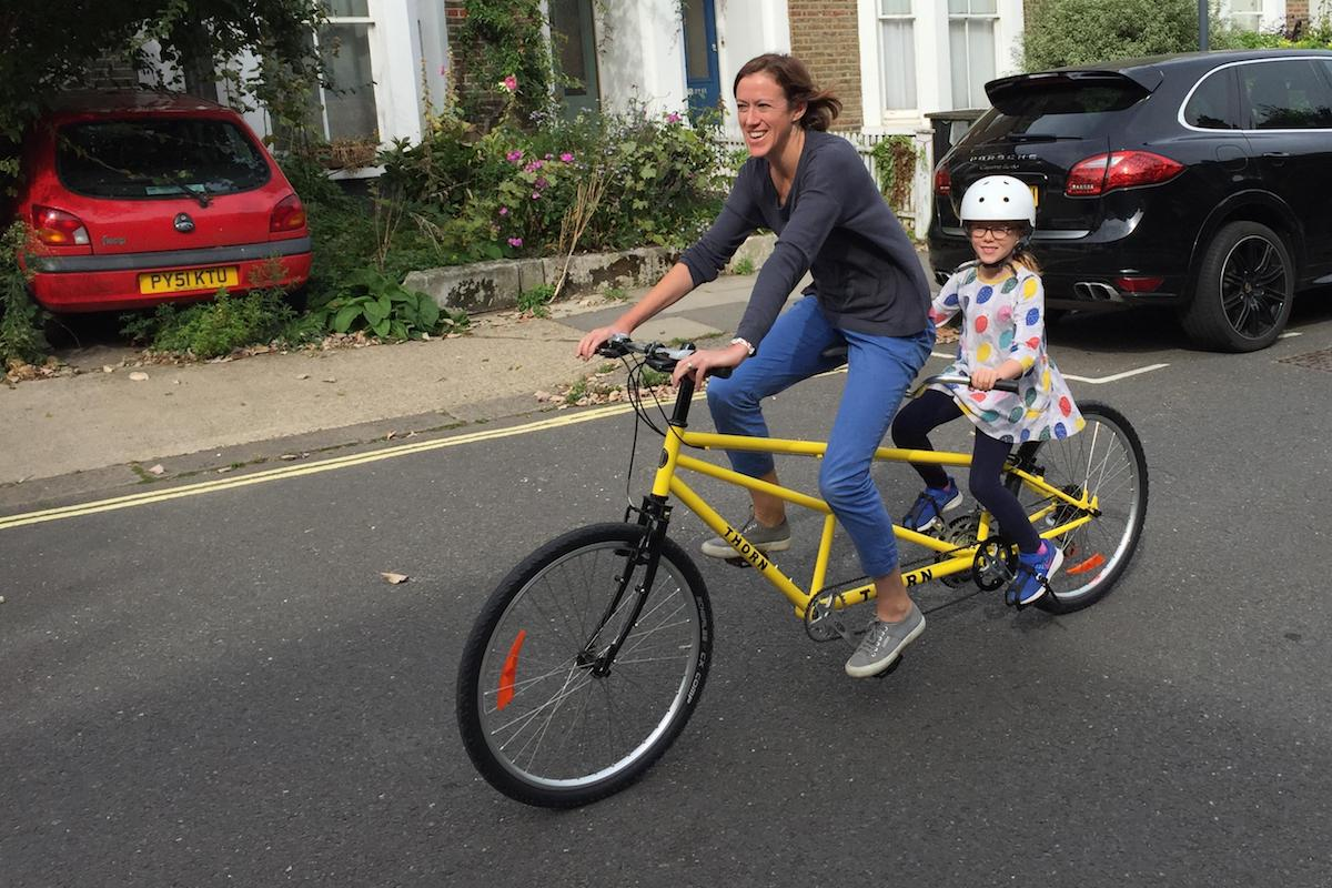 Woman and child cycle on a tandem bike down a quiet street