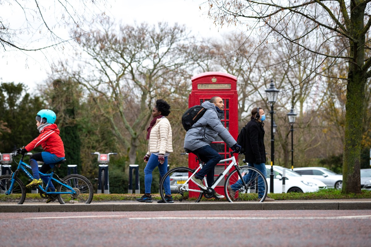 People walking and cycling past a Santander docking station and red phone box in Hyde Park