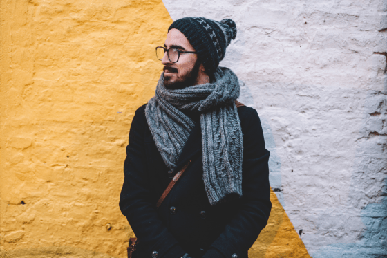 Man wrapped up warm standing in front of yellow wall
