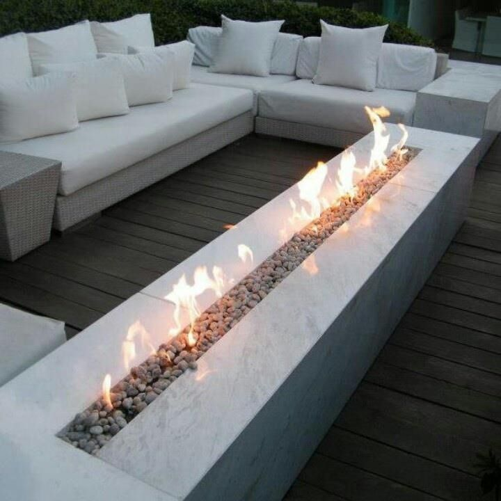 Outdoor Fireplace With White Cushioned Sofa