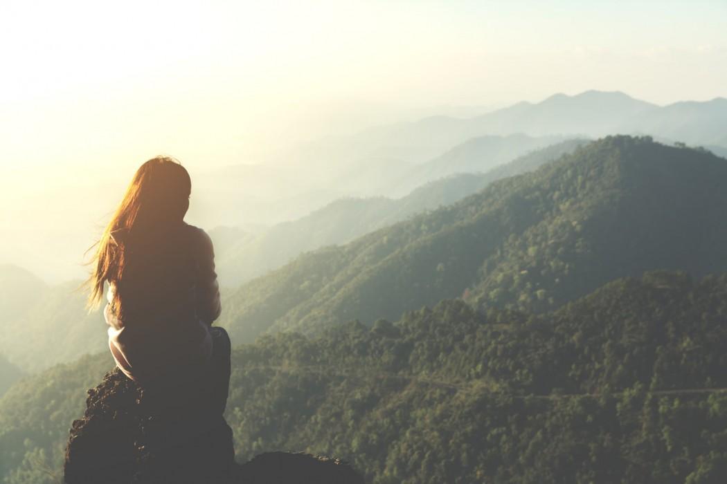 Mindful Travel - woman sitting on mountain