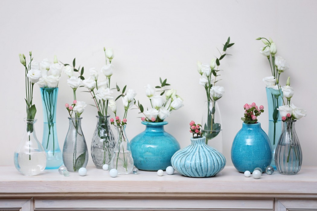 Fresh flowers in vases on mantelpiece