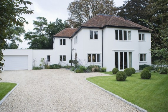 Large white detached house with gravel driveway