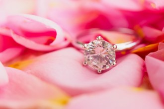 Diamond ring jewelry on pink rose petal