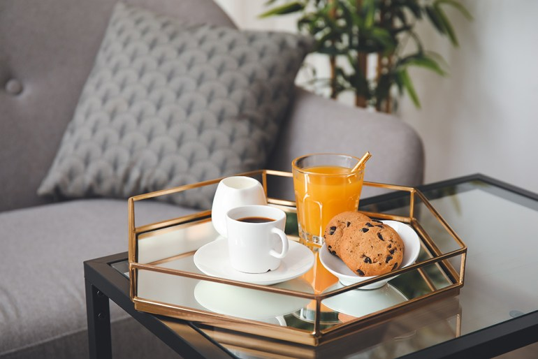 Stylish tray with drinks and biscuits placed on top