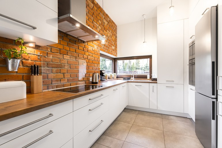 White slab (flat panelled) kitchen cupboards, brick wall, clear splashback and tiled flooring