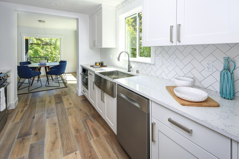 White kitchen cupboards and tiles. Stainless steel kitchen appliances and laminate flooring.