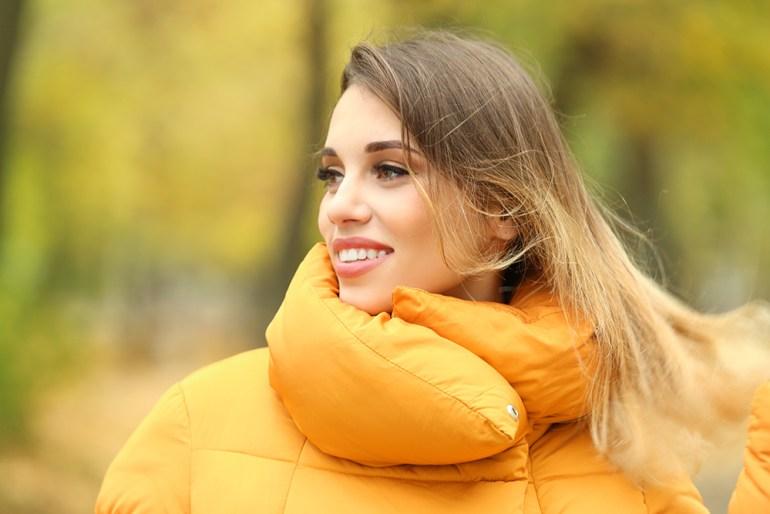 Women with brown hair wearing orange puffer jacket