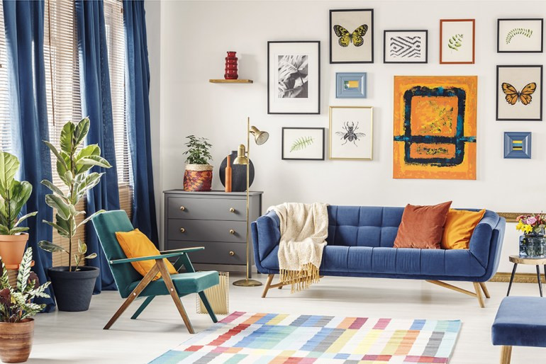 Colourful lounge with blue sofa and picture wall