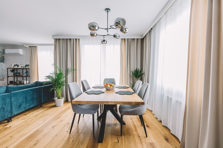 Dining area in open plan living room. Solid wood flooring, wooden dining table and grey chairs