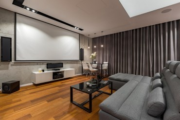 White minimalist living room with grey sofa and movie projector screen
