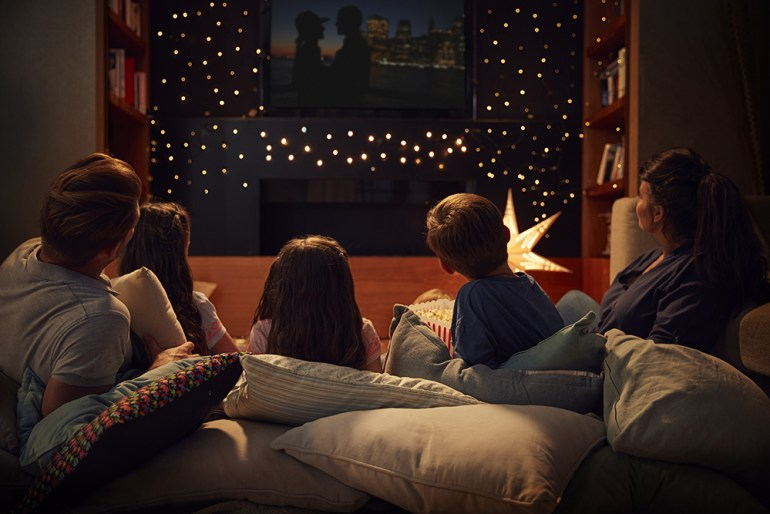 Family watching movies together. Resting on comfy sofa with large pillows