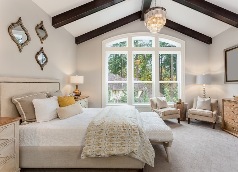 Large bedroom, vaulted ceiling with wood beams and chandelier.