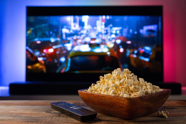 Large TV screen with bowl of popcorn on table