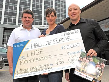 LHSF Executive Vice President John MacFarlane proudly accepts a cheque in the amount of $50,000 from London firefighters Allison Vickard and Bob Geilen, co-chairs of the Hall of Flame Calendar committee. (Photo by Mike Maloney, London Community News)