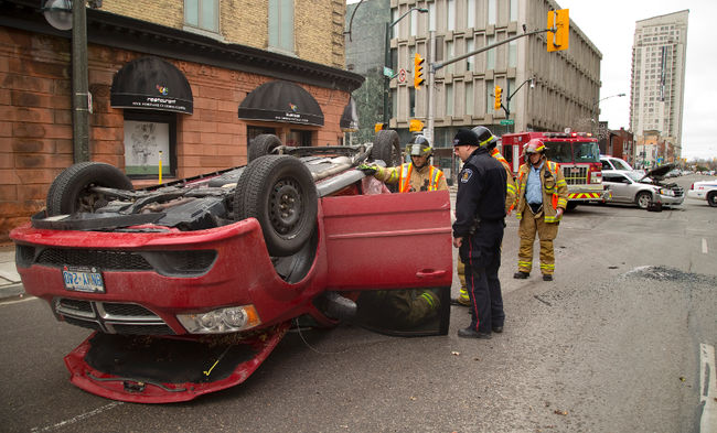 Const. Antoni Uchmanowicz talks to firefighters at the scene of a Sunday morning rollover at King and Richmond streets in London. Mike Hensen/The London Free Press/Postmedia Network
