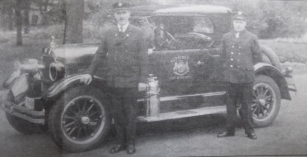 Fire Chief Jenner and Firefighter Hanley posing with Chief's car