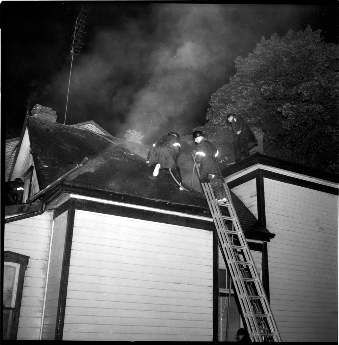 Three fire fighters on a roof extinguishing fire in the roof and attic