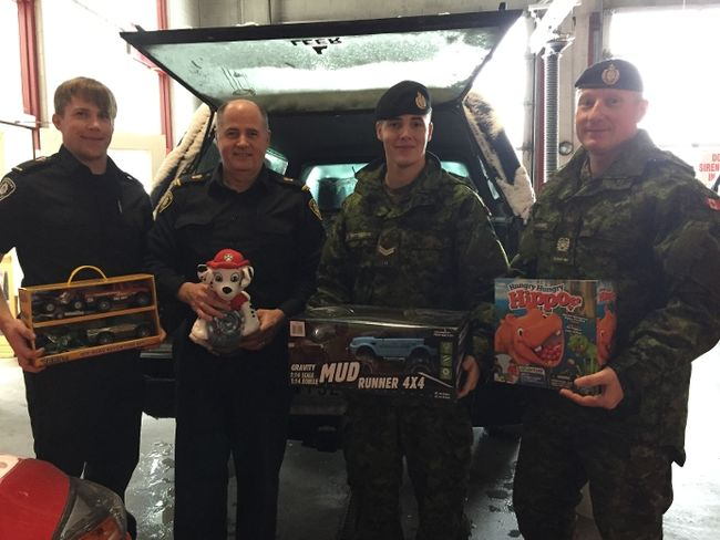 Firefighters and military personnel loading toys into vehicle