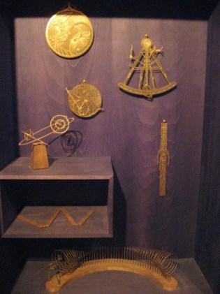 Bookcase of strange brass implements. Image: LKL