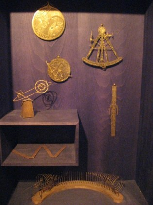 Bookcase of strange brass implements. Image: LKL