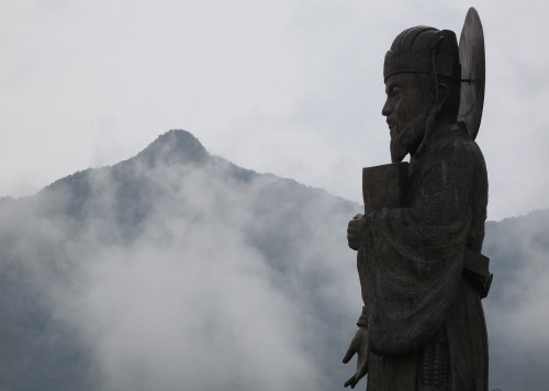 A statue of Heo Jun with Pilbongsan in the background
