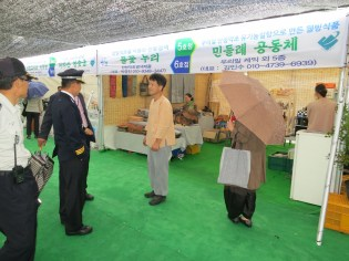 The chief of police inspects a stall of organically-dyed fabrics