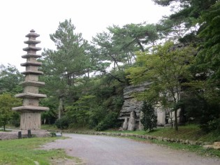 The first pagoda to greet you on the driveway: Treasure #796, a nine-storey stone pagoda. And to the right, Buddhist sculpture resting against the rock